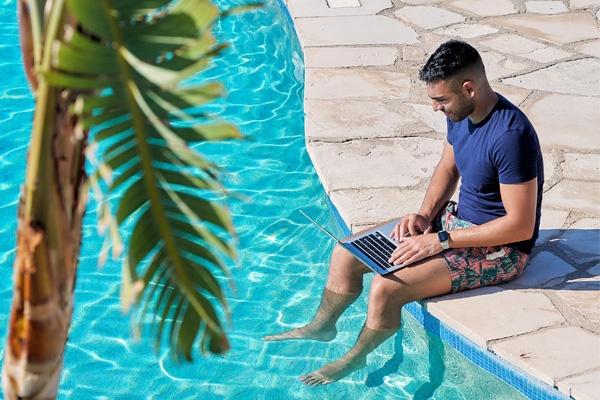 Man sitting at the rim of pool working on laptop, Cyprus - Amera Villas